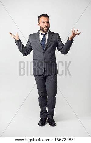 Embarrassed emotional businessman on a gray background