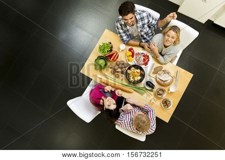 Group of oung people eating pizza and drinking cider in the modern interior view from above
