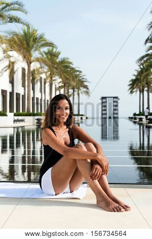 Beautiful young Indian woman on a tropical vacation sitting barefoot at the edge of a tranquil resort pool lined with palm trees smiling at the camera