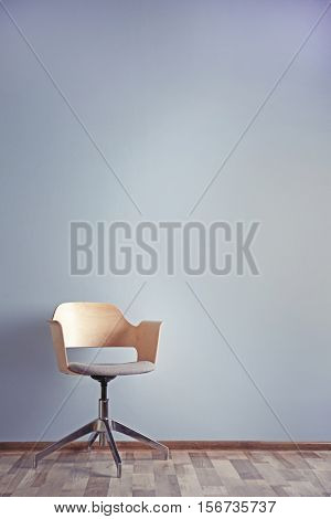 Simple interior with stool on blue wall background