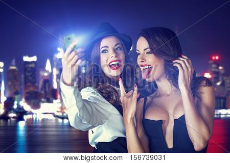 Young crazy sexy girlfriends taking selfie at night in city