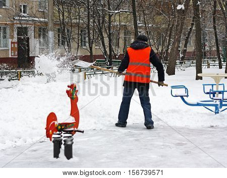 Snow removal in winter on the Playground. A man with a shovel clearing snow from the tracks.