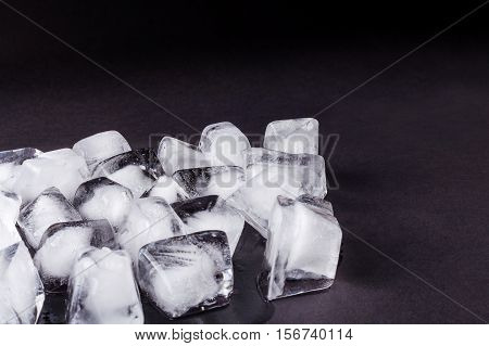 Bunch of ice cubes on a dark background. Chaotic scattered icicles on a black background. Winter background. New Year pattern.