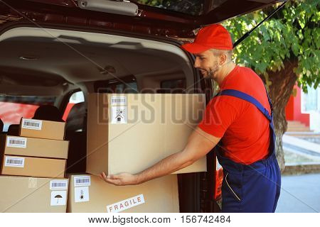 Delivery man unloading parcel from car