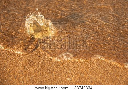 One stone on the yellow sand against the backdrop of a breaking wave