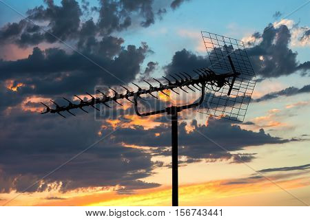 old TV antenna silhouette on evening blue cloudy sky background