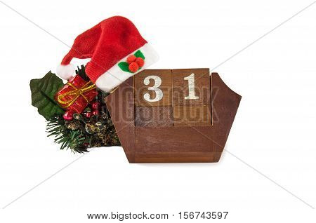 December 31st. Cube shape vintage wooden calendar for December 31 with Santa hat Christmas decorations and gift box isolated over white. New year at work concept. Copyspace for text.