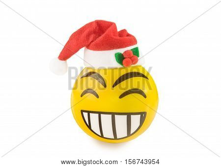 Yellow toy ball in the form of laughing emoticon with Santa hat isolated over white. Christmas mood concept.