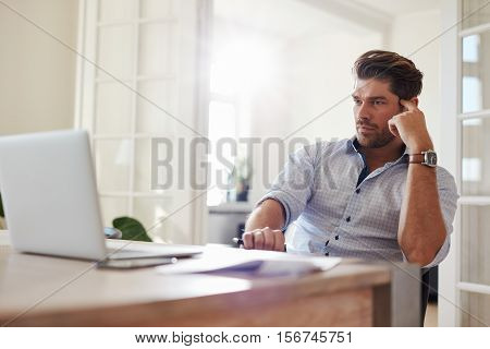 Businessman At Home Office Looking At Laptop And Thinking