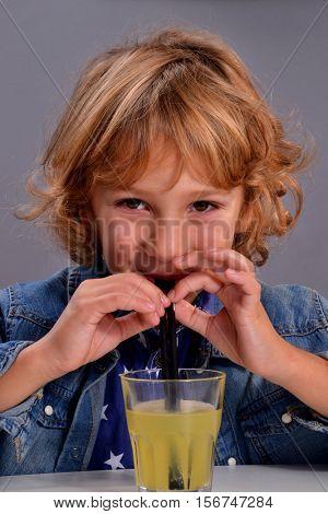 Little kid drinking orange soda with straw.