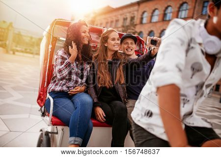 Young friends taking selfie on tricycle ride. Young women and man riding on tricycle bike and taking self portrait.
