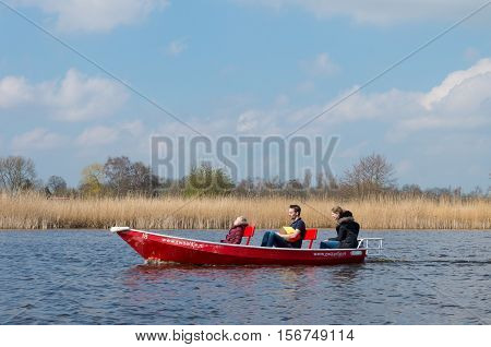 GIETHOORN NETHERLANDS - APRIL 3 2016: Unknown family enjoying their boating trip around Giethoorn also called the Venice of the netherlands