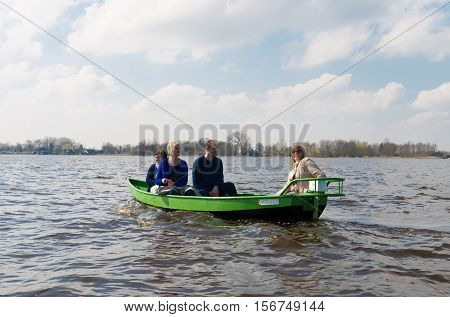 GIETHOORN NETHERLANDS - APRIL 3 2016: Unknown people enjoying their boating trip around Giethoorn also called the Venice of the netherlands