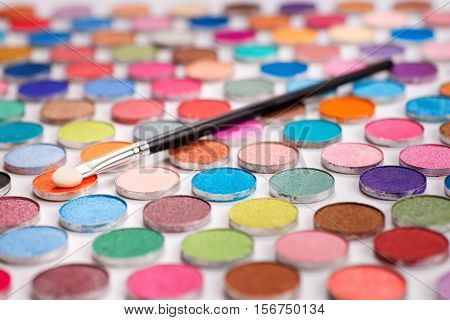 Cosmetic sponge brush laying over large group of colored eyeshadows. Selective focus