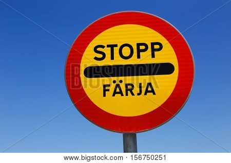 Swedish road sign stop at ferry berth against blue sky.