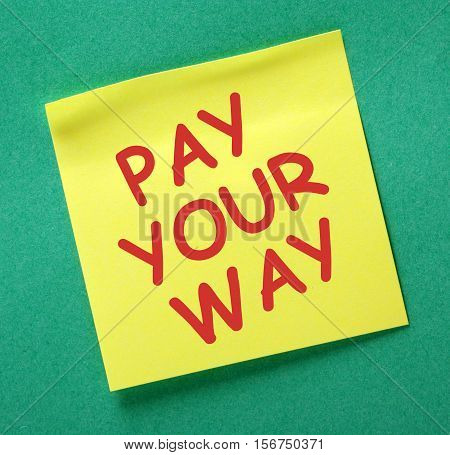 The phrase Pay Your Way in red text on a yellow sticky note as a reminder to earn enough to cover your expenses and live within your means