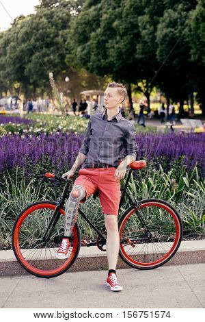 Hipster with bycicle in park near purple flowers.