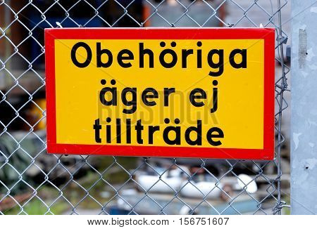 Close up of yellow sign on a fence with text in Swedish No admission for unauthorized (Obehoriga ager ej tilltrade)