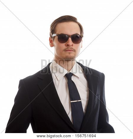 A young adult in a suit wearing a tie and sunglasses