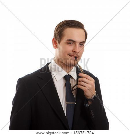 A flirtatious young man in a suit biting his shades