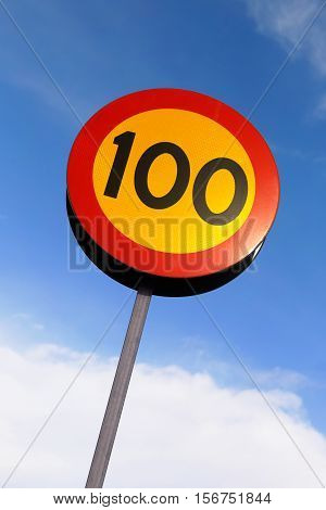 Speed limit 100 road sign against blue sky.