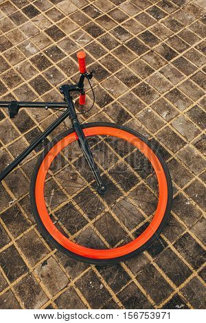 One wheel of red bycicle on floor.