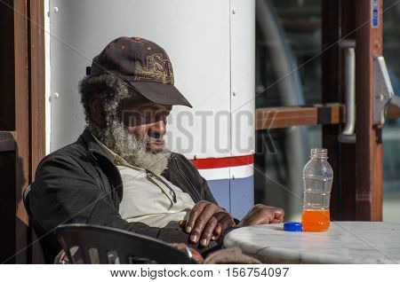 Old Beggar Sleeping On Cafe Chair At Pier 39. San Francisco. Usa