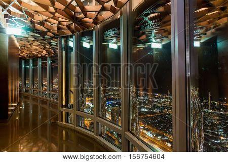 DUBAI - NOVEMBER 08 2016. The interior of the Burj Khalifa in 125 floor. Wooden decorated ceiling in the shape of a star. Dubai United Arab Emirates. The interior of the Burj Khalifa in 125 floor. Observation glass patio at night Dubai.