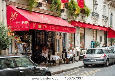 PARIS FRANCE - MAY 21 2016: Cafe brasserie restaurant Flottes in central Paris on 2 rue Cambon with people eating and having fun on the oudside tables