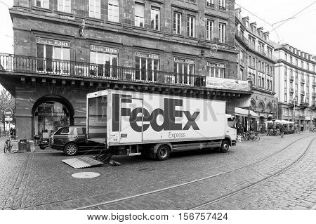 STRASBOURG FRANCE - 8 NOV 2016: New FEDEX white truck unloading merchandise in beautiful city environment. FedEx is one of the leading parcel services worldwide with main competitors as DHL and UPS