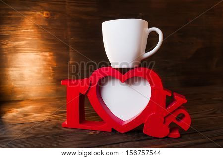 red photoframe with a cup on wooden background