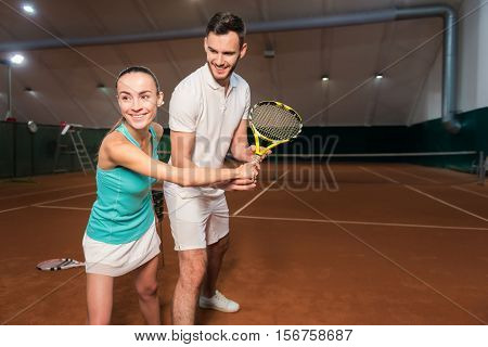 Involved in activity. Overjoyed smiling young friends holding racket and learning to play tennis in indoor court while expressing gladness