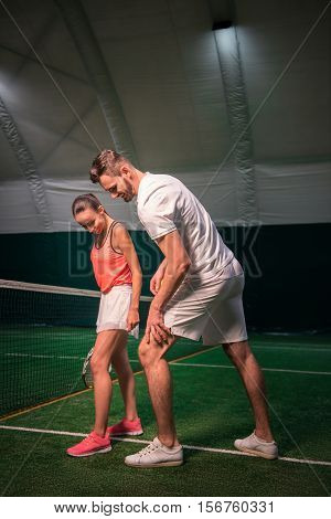 This position. Positive professional tennis instructor showing a young woman how to stand and going to play teenis together in the indoor tennis court