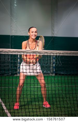 Involved in jubilation. Positive delighted beautiful woman holding racket and playing tennis in indoor court