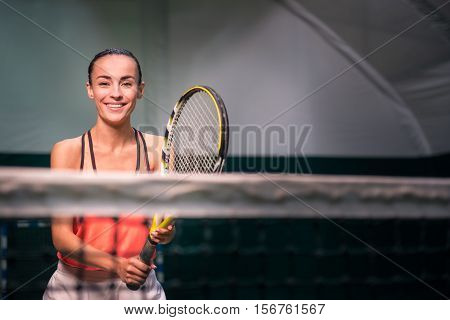 Play with me. Positive charming smiling young woman holding racket and playing tennis while training t in indoor court