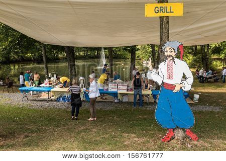 Silver Spring, USA - September 17, 2016: Cut out of Cossack man with grill sign and picnic area at Ukrainian festival