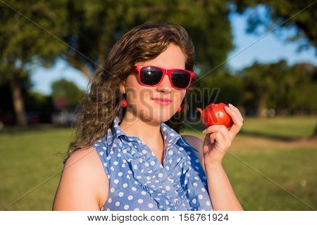 Young girl smiling in outdoor park holding tomato and wearing red sunglasses