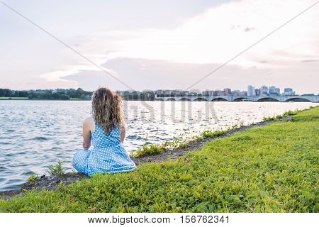 Young woman sitting on grass overlooking Potomac River with Arlington Memorial bridge