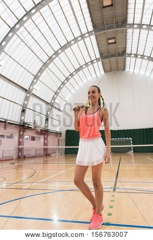 Share your emotions. Positive content charming woman holdign tennis racket on the shoulder and lookign aside while going to play tennis