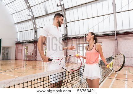 Glad to play together. Cheerful smiling young tenis players standign near net and resting after set while discussing it