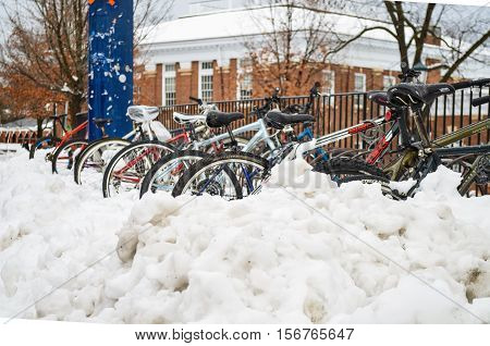 Charlottesville, USA - March 6, 2013: Bikes in rack covered in snow on University of Virginia campus grounds