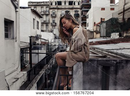 Sad girl melancholic smoking sitting on the roof