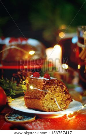 Piece of christmas pudding cake on white saucer decorated with berries sprinkled with sugar powder. Traditional christmas food.
