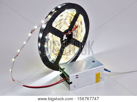 Spool of luminous LED strip light connected to Power Supply Adapter Driver.