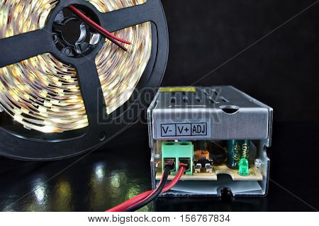 Close-up Shining LED Strip Light on a reel near voltage converter black background.