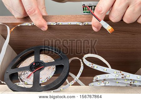 Close-up of a hand electrician installation LED strip inside the cabinet.