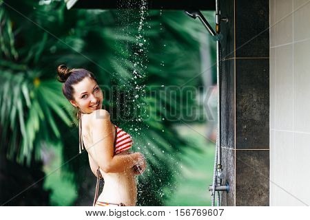 Shower On Beach. Beautiful Fit Woman Taking Shower At Swimming Pool. Girl With Sexy Body In Swimsuit Showering Under Water. Cleaning Body And Skin Outdoors At Luxury Spa Resort In Summer