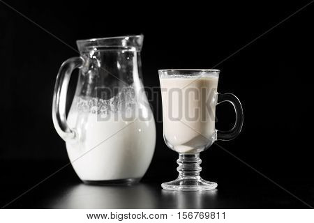 Milk is from jug bottle into the glass on black background