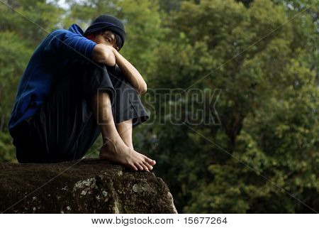 Troubled asian man sitting on rock outdoors