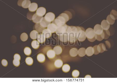 Retro blur bokeh defocused decoration lights of golden color on black background. Defocused abstract gold colour lights background for Christmas postcard design. Blurred Xmas Lights background.